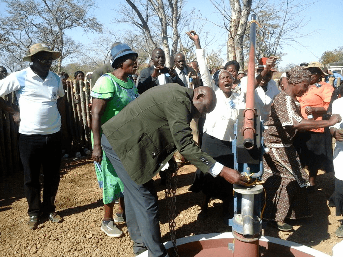 people celebrating the opening of a borehole as part of HelpAge Zimbabwe Water and Sanitation Campaign