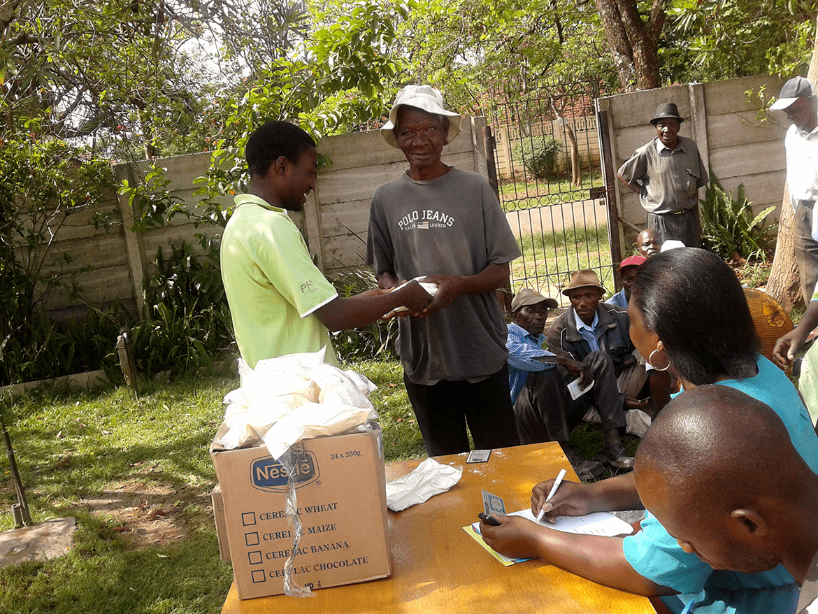 HelpAge Zimbabwe Director and Volunteering team giving donation to a golden ager
