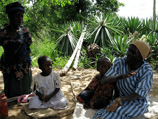 A rural old african woman sitting with her family thanking HelpAge Zimbabwe for her successful eye operation