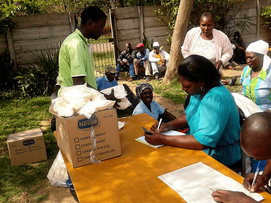 HelpAge Zimbabwe Volunteers serving old people with clothing
